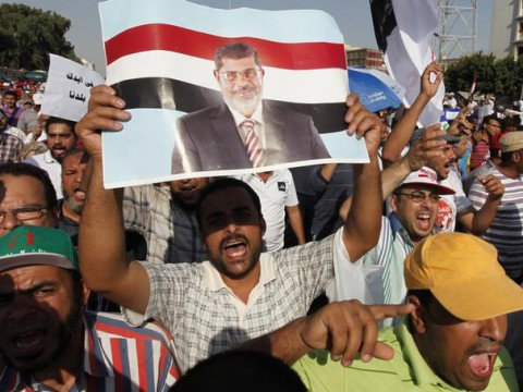 Supporters of Egyptian President Mursi shout slogans during protest around Raba El-Adwyia mosque square in Cairo