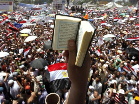 An Egyptian protester holds up a Koran while participating in a rally at Tahrir square in Cairo