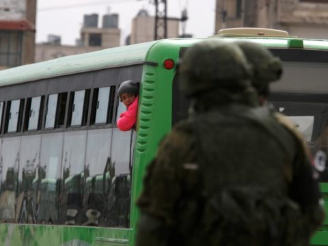 A boy rides a bus to evacuate the besieged Waer district in the central Syrian city of Homs