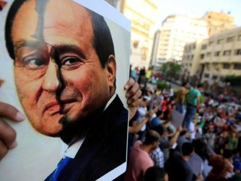 FILE PHOTO: A poster show a placard with the faces of Hosni Mubarak and Abdel Fattah al-Sisi is seen by activists during a protest in downtown Cairo